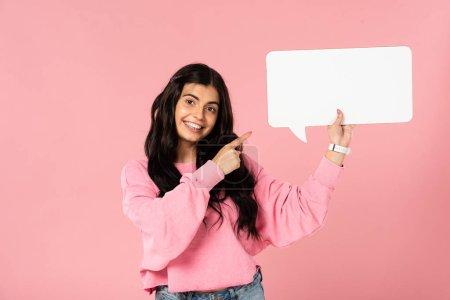 Photo pour Fille souriante pointant vers bulle de parole vide, isolé sur rose - image libre de droit
