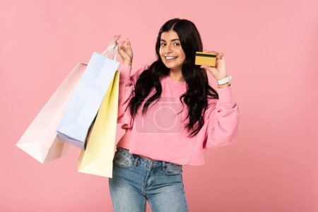 Photo for Beautiful smiling woman holding credit card and shopping bags, isolated on pink - Royalty Free Image