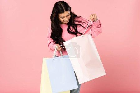Photo pour Belle femme heureuse regardant dans des sacs à provisions, d'isolement sur le rose - image libre de droit