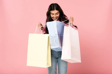 Photo for Attractive smiling girl holding shopping bags, isolated on pink - Royalty Free Image