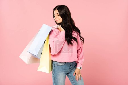 Photo for Attractive woman holding shopping bags, isolated on pink - Royalty Free Image