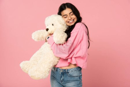 Photo pour Souriant jeune femme étreignant ours en peluche, isolé sur rose - image libre de droit