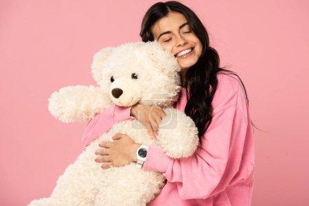 Photo pour Belle fille souriante étreignant ours en peluche, isolé sur rose - image libre de droit
