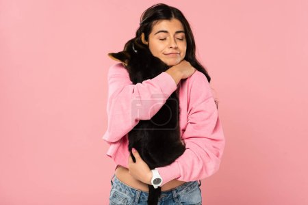 Photo for Cheerful girl hugging cute puppy, isolated on pink - Royalty Free Image