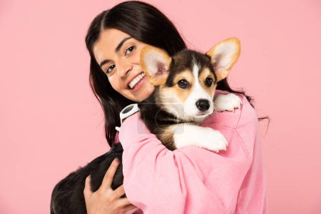 Photo for Cheerful girl holding Welsh Corgi puppy, isolated on pink - Royalty Free Image