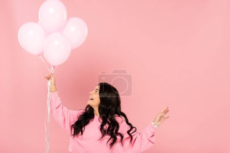 Photo for Beautiful excited girl holding pink balloons, isolated on pink - Royalty Free Image