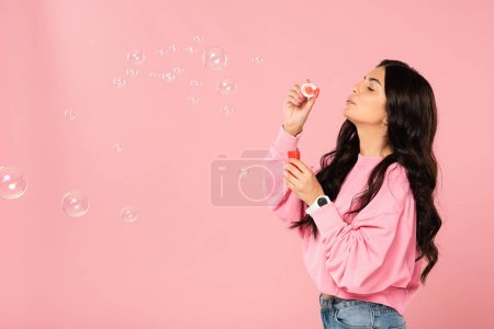 Photo for Cheerful woman blowing soap bubbles isolated on pink - Royalty Free Image