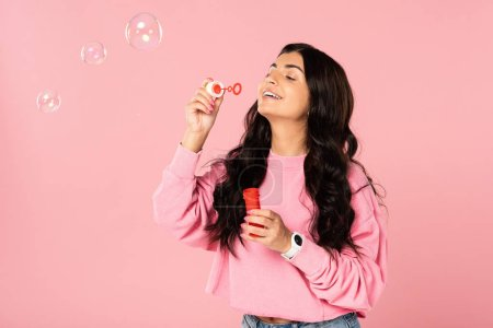 Photo for Beautiful brunette girl blowing soap bubbles isolated on pink - Royalty Free Image
