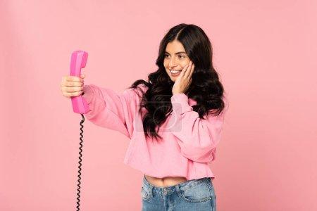 Photo pour Fille attirante de sourire regardant le téléphone rétro d'isolement sur le rose - image libre de droit