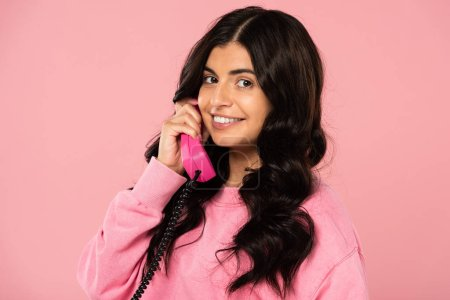 cheerful girl talking on retro telephone isolated on pink