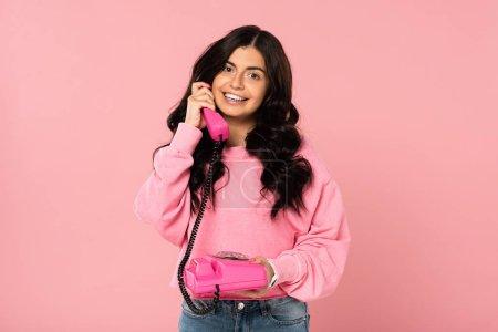 Photo pour Fille attirante de sourire parlant sur le téléphone rétro d'isolement sur le rose - image libre de droit