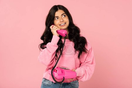 Photo for Attractive girl talking on retro telephone isolated on pink - Royalty Free Image