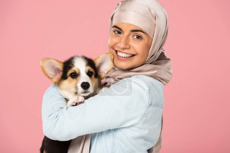 Photo pour Femme musulmane souriante dans le hijab tenant chiot gallois Corgi, isolé sur rose - image libre de droit