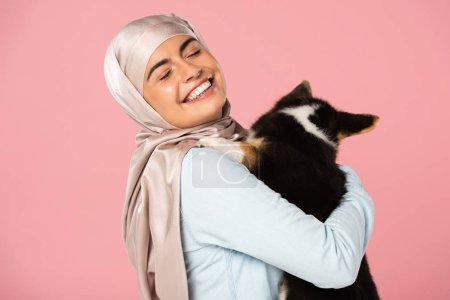 Photo pour Gai arabian fille dans hijab tenant chiot mignon, isolé sur rose - image libre de droit