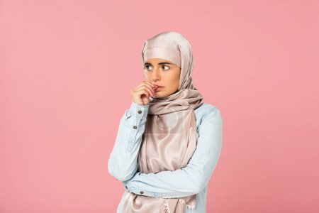 Photo for Beautiful stressed muslim girl in hijab, isolated on pink - Royalty Free Image