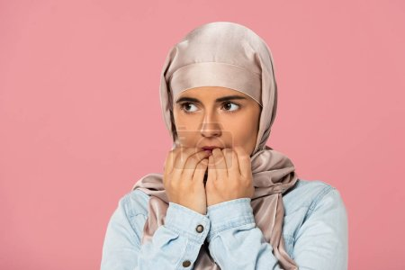 Photo pour Belle fille musulmane effrayée dans les ongles mordants de hijab, d'isolement sur le rose - image libre de droit