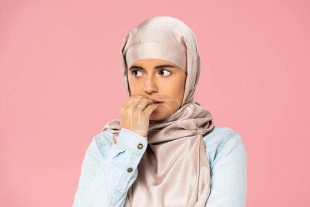 Photo pour Fille musulmane effrayée dans les ongles mordants de hijab, d'isolement sur le rose - image libre de droit