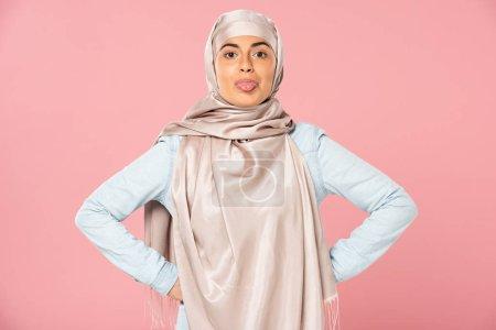 Photo pour Belle femme musulmane drôle dans la langue collante de hijab dehors, d'isolement sur le rose - image libre de droit