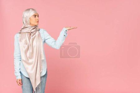 Photo pour Belle femme musulmane dans le hijab affichant quelque chose, isolé sur le rose - image libre de droit