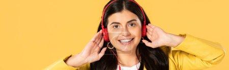 Photo pour Jeune femme souriante écoutant la musique avec des écouteurs, d'isolement sur le jaune - image libre de droit