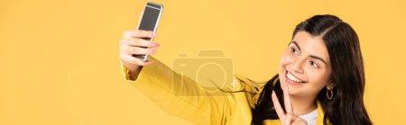 Photo pour Fille heureuse montrant signe de paix tout en prenant selfie sur smartphone, isolé sur jaune - image libre de droit