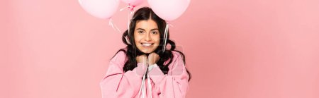 Photo for Excited brunette woman holding pink balloons, isolated on pink - Royalty Free Image