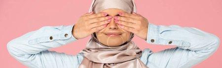 Photo pour Fille musulmane de sourire dans les yeux de fermeture de hijab, d'isolement sur le rose - image libre de droit