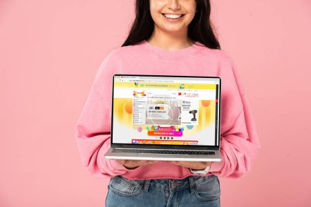 Photo pour KYIV, UKRAINE - 30 JUILLET 2019 : vue recadrée d'une jeune fille souriante tenant un ordinateur portable avec un site Web aliexpress à l'écran, isolée sur rose - image libre de droit