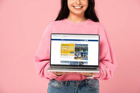KYIV, UKRAINE - 30 JUILLET 2019 : vue recadrée d'une jeune fille souriante tenant un ordinateur portable avec site de réservation à l'écran, isolée sur rose