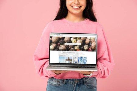 Photo pour Kiev, Ukraine - 30 juillet 2019: vue recadrée de fille souriante tenant l'ordinateur portable avec le site Web de depositphotos sur l'écran, d'isolement sur le rose - image libre de droit