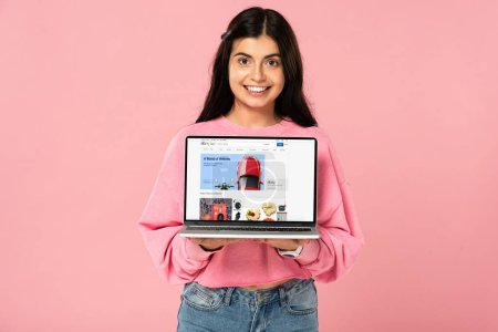 Photo for KYIV, UKRAINE - JULY 30, 2019: smiling girl holding laptop with ebay website on screen, isolated on pink - Royalty Free Image