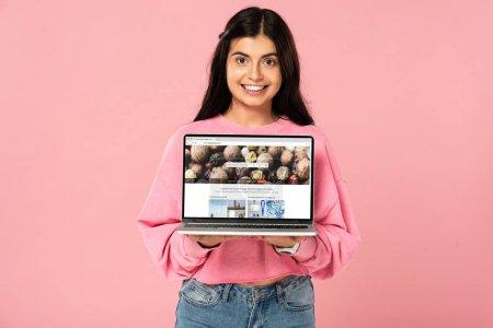 Photo pour Kiev, Ukraine - 30 juillet 2019: fille souriante retenant l'ordinateur portatif avec le site web de depositphotos à l'écran, d'isolement sur le rose - image libre de droit