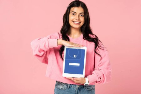 Photo for KYIV, UKRAINE - JULY 30, 2019: smiling girl holding digital tablet with facebook app on screen, isolated on pink - Royalty Free Image