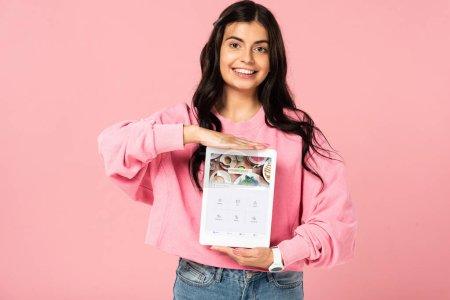 Photo pour KYIV, UKRAINE - 30 JUILLET 2019 : fille souriante tenant une tablette numérique avec application quadratique à l'écran, isolée sur rose - image libre de droit
