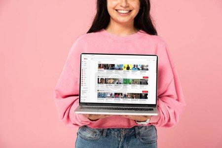 Photo pour KYIV, UKRAINE - 30 JUILLET 2019 : vue recadrée d'une jeune fille souriante tenant un ordinateur portable avec un site Web youtube à l'écran, isolée sur rose - image libre de droit