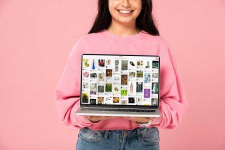 Photo pour KYIV, UKRAINE - 30 JUILLET 2019 : vue recadrée d'une jeune fille souriante tenant un ordinateur portable avec un site Web pinterest à l'écran, isolée sur rose - image libre de droit