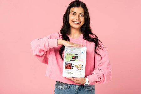 KYIV, UKRAINE - JULY 30, 2019: smiling girl holding digital tablet with ebay app on screen, isolated on pink