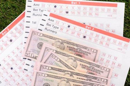 Photo pour Billets en dollars et listes de paris sur le gazon vert, concept de paris sportifs - image libre de droit