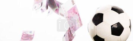 Foto de Foto panorámica del balón de fútbol cerca de la caída de los billetes en dólares aislados en blanco, concepto de apuestas deportivas. - Imagen libre de derechos