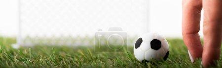 Photo pour Vue recadrée des doigts féminins près du ballon de football jouet et des portes de football isolés sur blanc, concept de paris sportifs - image libre de droit