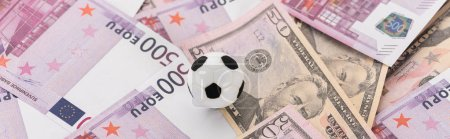 Photo for Panoramic shot of toy soccer ball on dollar and euro banknotes, sports betting concept - Royalty Free Image