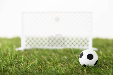 Photo for Selective focus of toy soccer ball and football gates on green field isolated on white, sports betting concept - Royalty Free Image