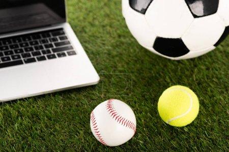 Photo pour Soccer, balles de baseball et de tennis près d'un ordinateur portable sur gazon vert, concept de paris sportifs - image libre de droit