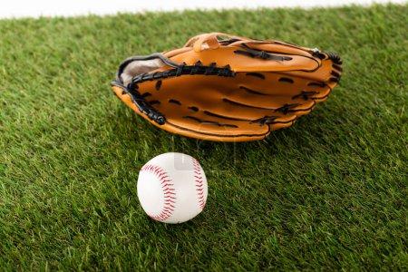 Foto de El guante de béisbol y el balón sobre hierba verde aislado en blanco, concepto de apuestas deportivas. - Imagen libre de derechos