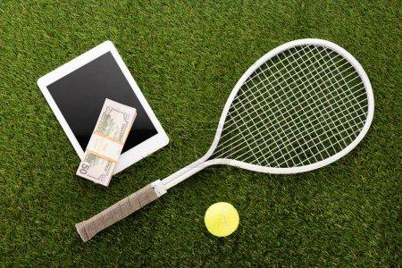 Photo pour Vue du dessus de la raquette de tennis et de la balle près de la tablette numérique et des billets en euros sur herbe verte, concept de paris sportifs - image libre de droit