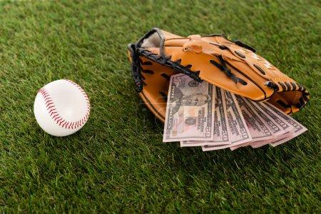 Photo pour Billets de dollars dans un gant de baseball près d'un ballon sur gazon vert, concept de pari sportif - image libre de droit