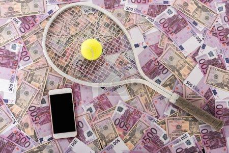 Photo pour Vue du haut du smartphone avec écran vierge, raquette de tennis et balle sur billets en euros et en dollars, concept de paris sportifs - image libre de droit