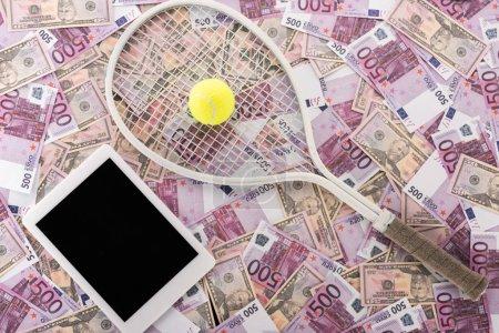 Photo pour Vue du haut de la tablette numérique avec écran vierge, raquette de tennis et balle sur billets en euros et en dollars, concept de paris sportifs - image libre de droit