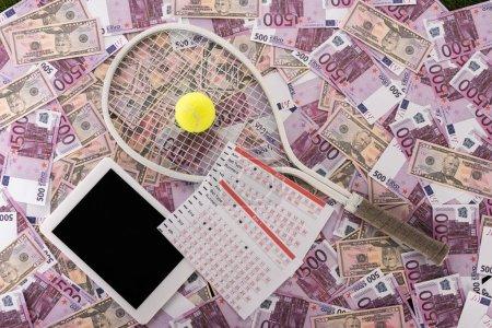Photo pour Vue du haut de la tablette numérique, listes de paris, raquette de tennis et balle sur billets en euros et en dollars, concept de paris sportifs - image libre de droit