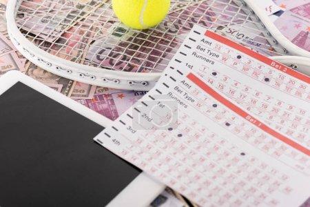 Photo pour Tablette numérique, listes de paris, raquette de tennis et balle sur billets en euros et en dollars, concept de paris sportifs - image libre de droit